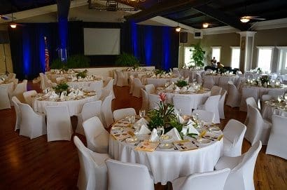 Ballroom set-up corporate style with white linens and chair covers including place settings and audio visual set-up.