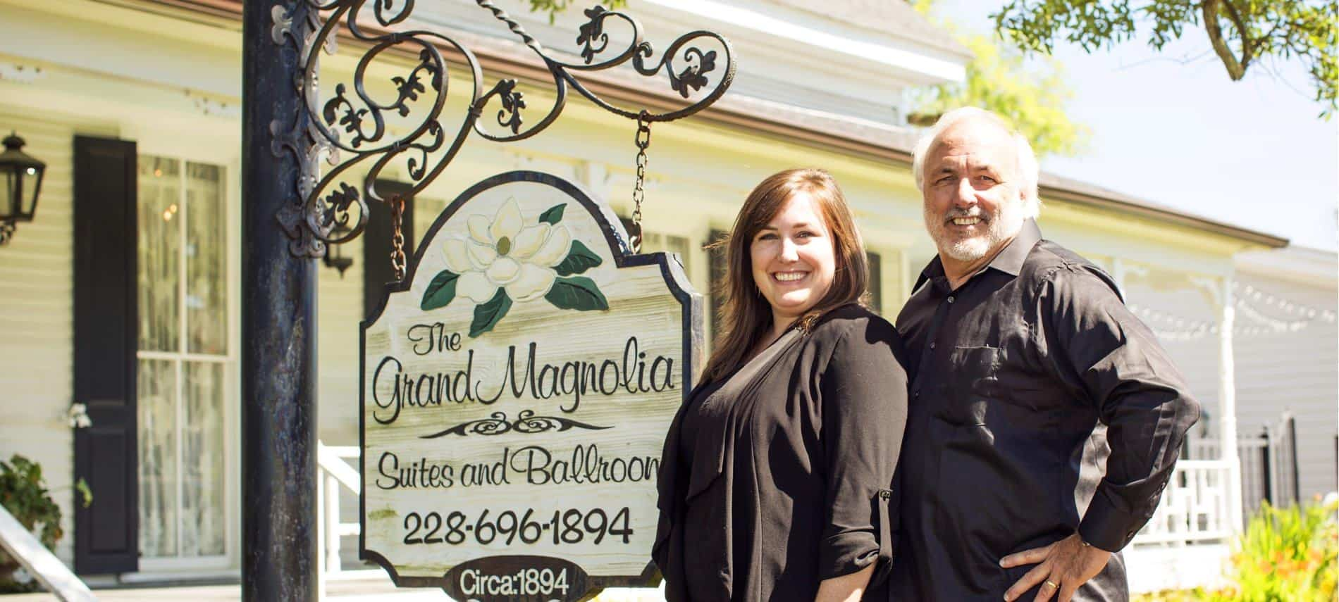 Owners, a man and woman, smiling outside standing next to the a hanging sign that says: The Grand Magnolia Suites and Ballroom 228-696-1894 Circa 1894