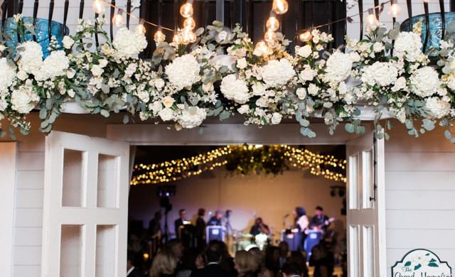 Double glass French doors swung open with large white flowers hanging overhead with view of wedding band and twinkle lights inside