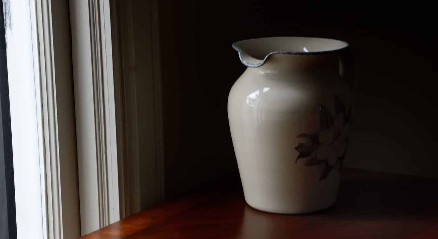 Large white vase sitting on a wood table next to a window