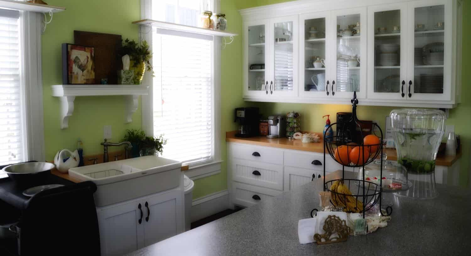 Kitchen with light green walls, white cabinets and shelves, wood tops, two windows and center island