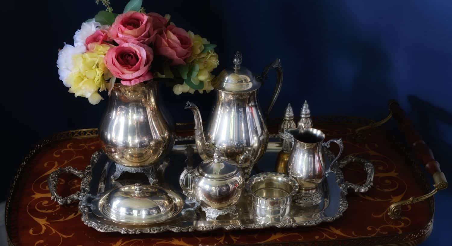 Silver tea set on a silver tray next to vase of fresh pink, yellow, and white flowers