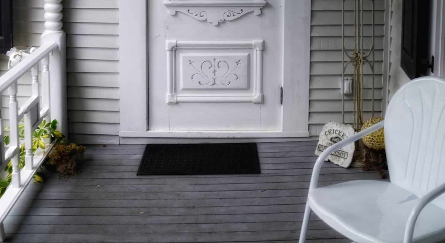 Covered porch with white railing, white chair and white entry door