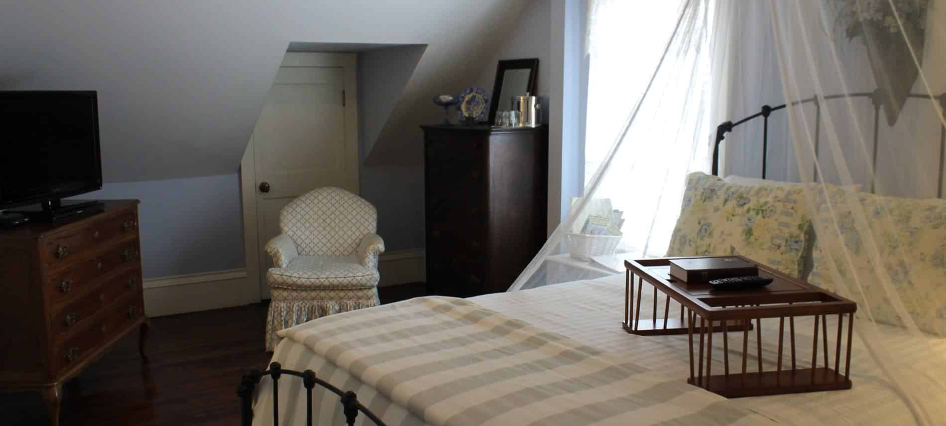 Cape Cod guest room, slanted ceiling, wood floor, window, metal bed with sheer white canopy, upholstered chair, dresser and TV