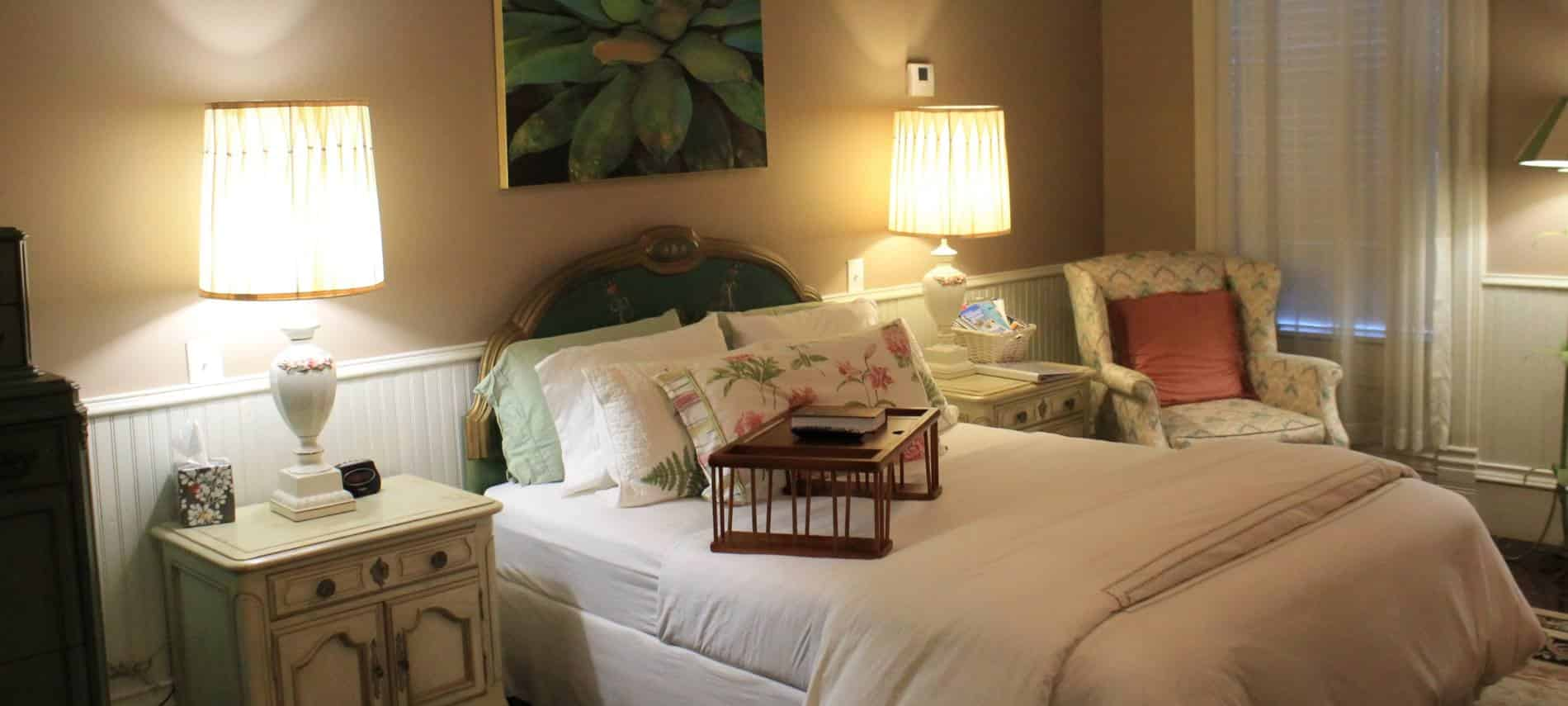 Garden guest room, tan walls, white beadboard, window with sheers, gold headboard and white bedding, nightstands with lamps, corner chair
