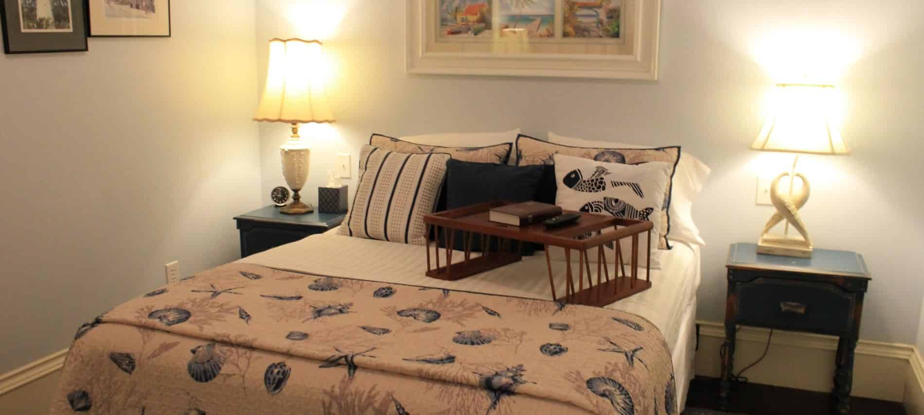 Key West guest room, bedding with seashells, two nightstands with lamps, tray with book and remote, beach photo collage on wall