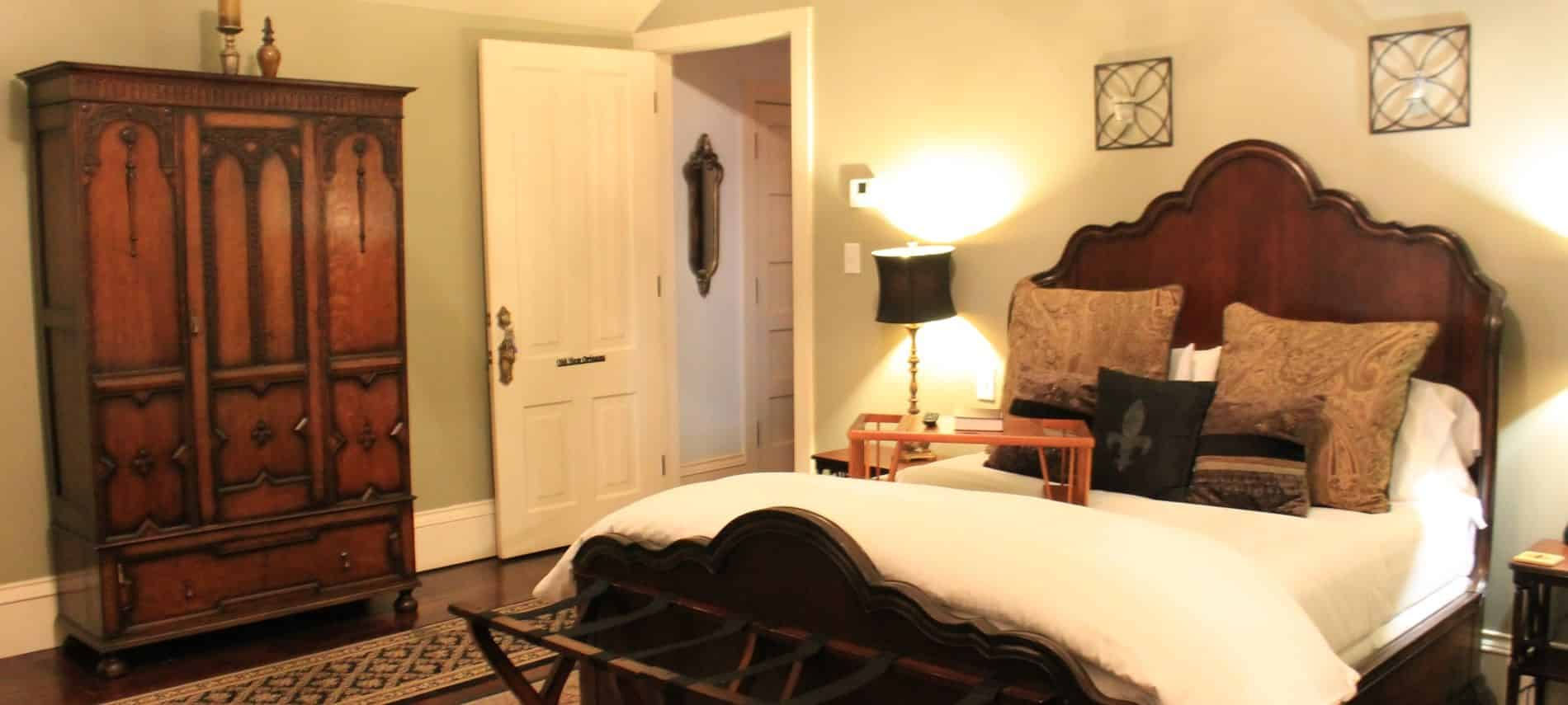 New Orleans guest room with light green walls, scalloped wood bed with white bedding, nightstand with lamps and tall armoire