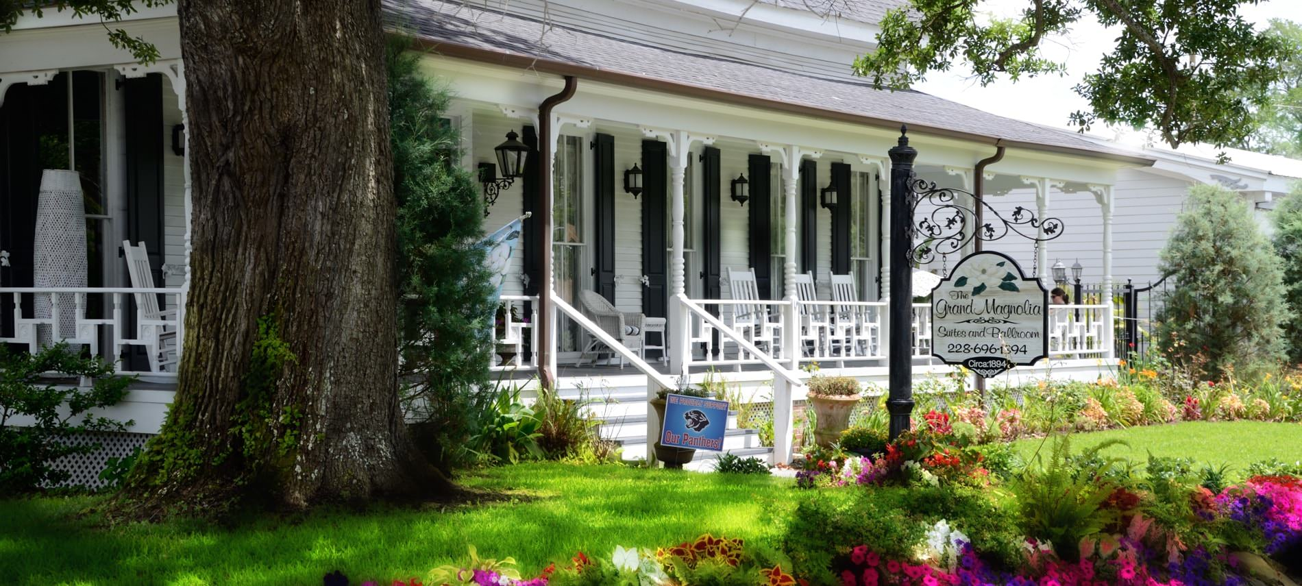 Exterior view, white sided home with covered porch, windows with black shutters amidst green grass, colorful flowers and mature tree