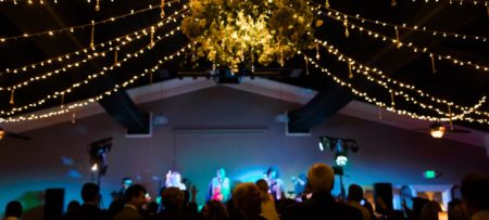 Wedding celebration at night with twinkle light ropes overhead and a stage with colorful lights