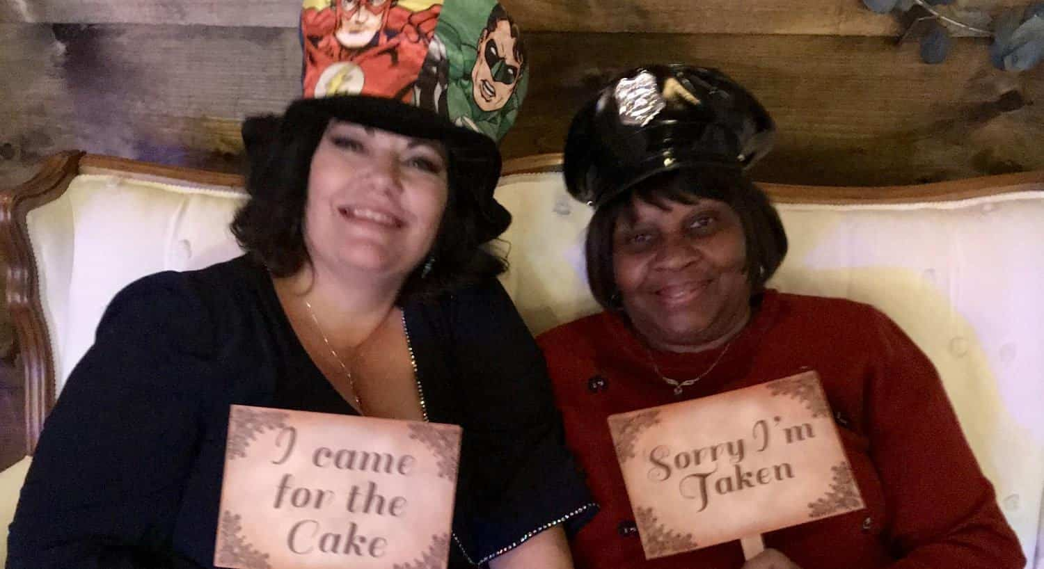 Two women smiling and wearing props for wedding reception photos