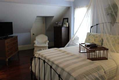 Cape Cod guest room with light blue walls, metal bed with striped bedding and sheer white canopy overhead