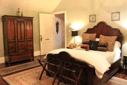 New Orleans guest room vaulted ceiling, dark scalloped wood bed, white bedding, nightstands with lamps and tall armoire