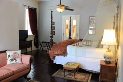 Savannah guest room with light walls, wood floor, dark four poster bed, ceiling fan, apricot sofa, and window