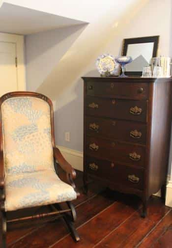 Cape Cod guest room with wide plank floors, slanted ceiling, dresser and rocking chair with cushions