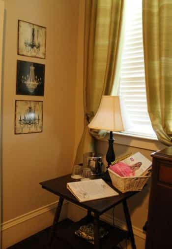 Charleston guest room corner - window with gold curtains and ivory blinds, small table with lamp, ice bucket, glasses and magazines