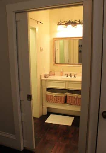 View of Charleston guest bath through a pocket door: white vanity with mirror, sconce lighting and shelf with baskets
