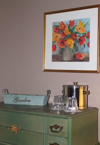 Garden guest room's green dresser topped with ice bucket and glass and picture of flowers in a gold frame overhead