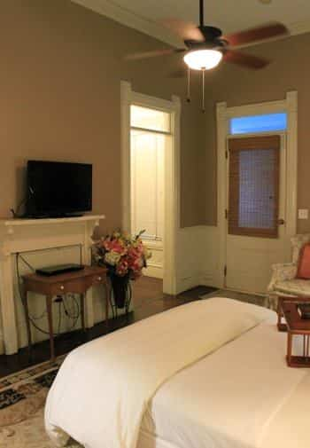 Garden guest room with tan walls, wood floors, bed with white bedding, ceiling fan, upholstered chair and TV