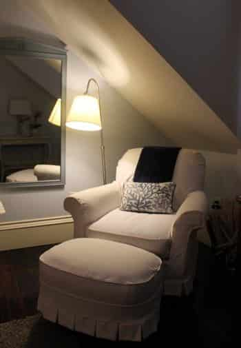 Key West guest room with slanted wall, upholstered chair and ottoman, wall mirror and floor lamp