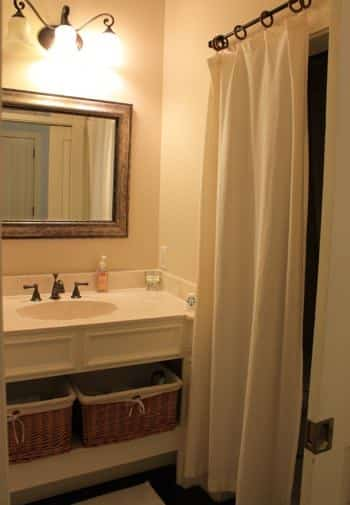 Key West guest bath with shower curtain, white vanity with mirror, sconce lighting and shelf with baskets