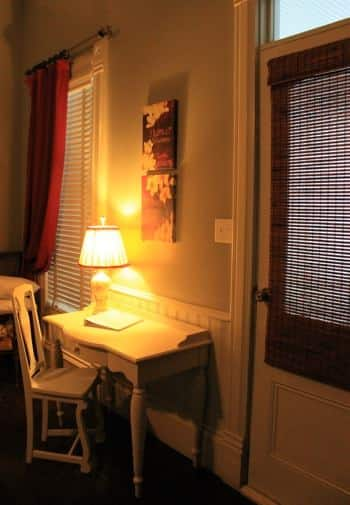 Little Gem guest room with window, exterior door, and white desk with lamp and chair