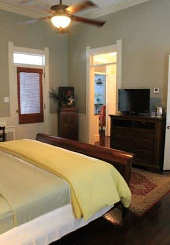 Little Gem guest room with light green walls, white beadboard, wood floors and sleigh bed, dresser, ceiling fan, and TV