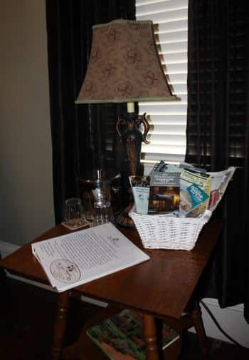 New Orleans guest bath side table with lamp, ice bucket, glasses and basket of magazines