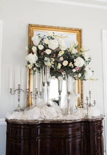 Dark wood console table topped with bunched white lace, two candelabras, two tall vases with flowers and gold rectangular mirror