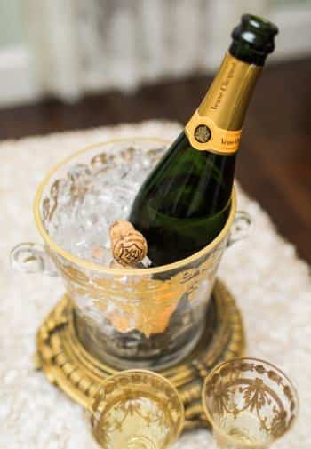 Bottle of champagne chilling in a gold and glass bucket with two gold and glass flutes nearby