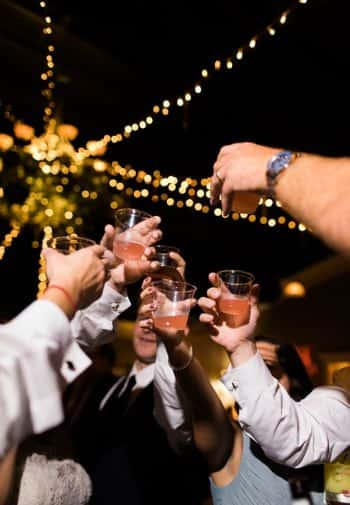 Several people from a bridal party raising glasses in a toast at night with twinkle lights overhead
