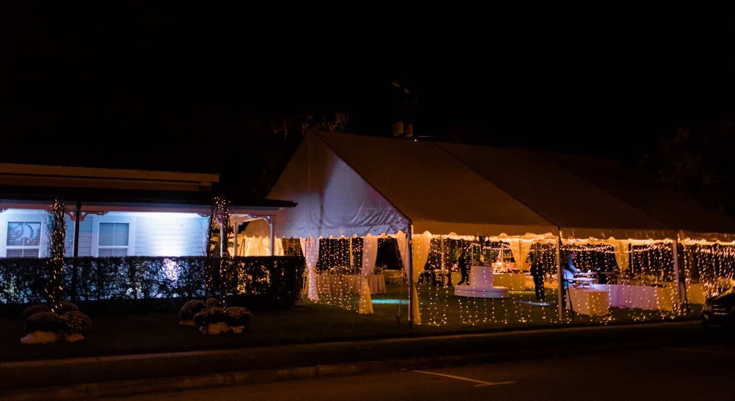 White wedding tent lined with twinkle lights at night