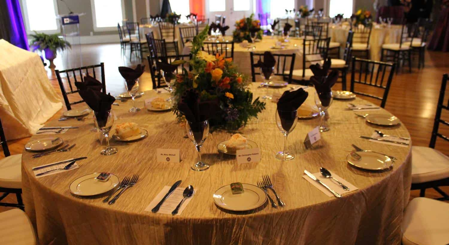 Ballroom with round tables topped with cloths, fresh flowers, and set for eight