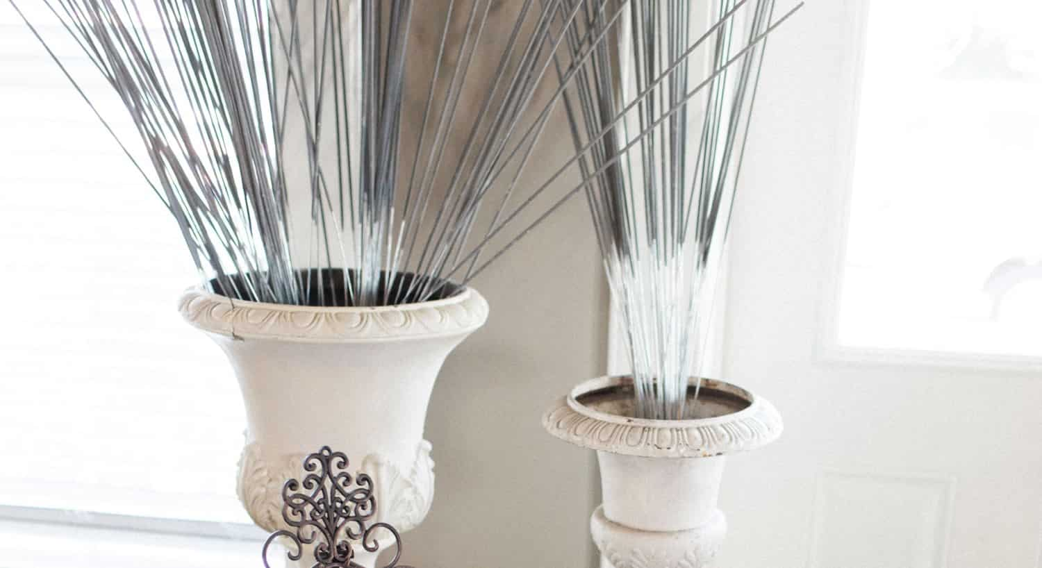 Two ivory decorative vases filled with tall gray-green sticks