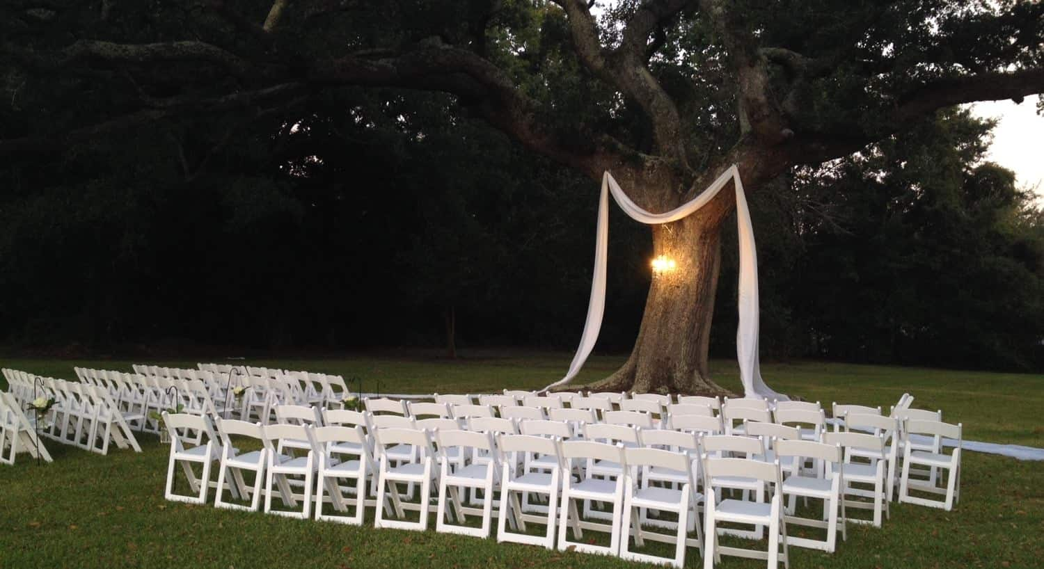 Outdoor wedding setup, rows of white chairs on grass, center aisle leading to tree with hanging light and sheer fabric