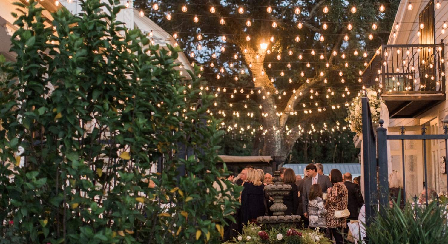 Wedding guests dining outside under rows of hanging twinkle lights