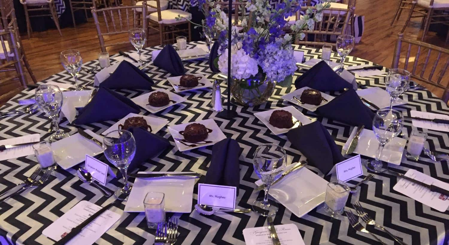 Overview of wedding table with black and white cloth, purple and white flowers, name cards, and chocolate desserts