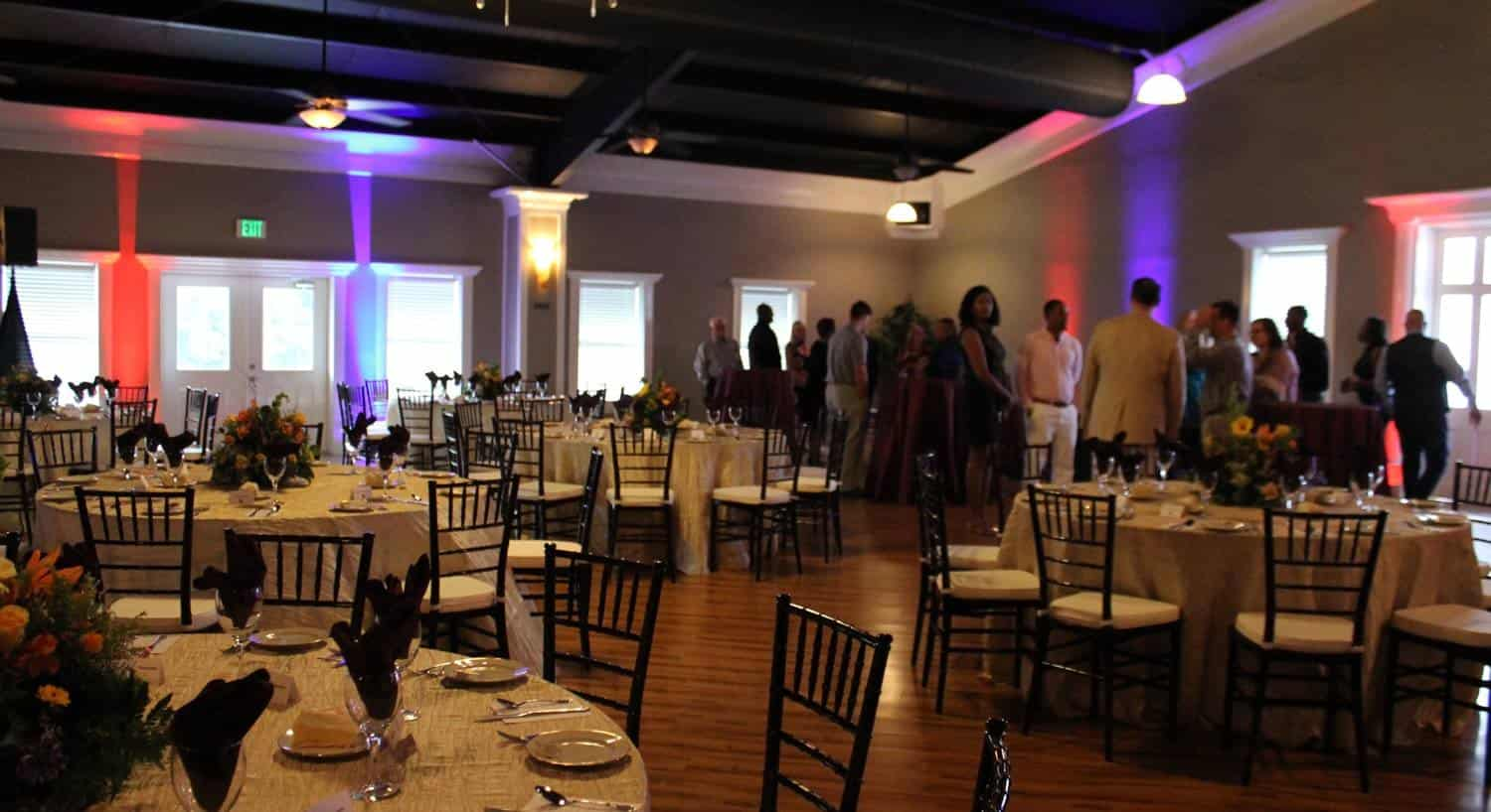 Ballroom with wood floor decorated with round tables and black chairs and colorful centerpieces