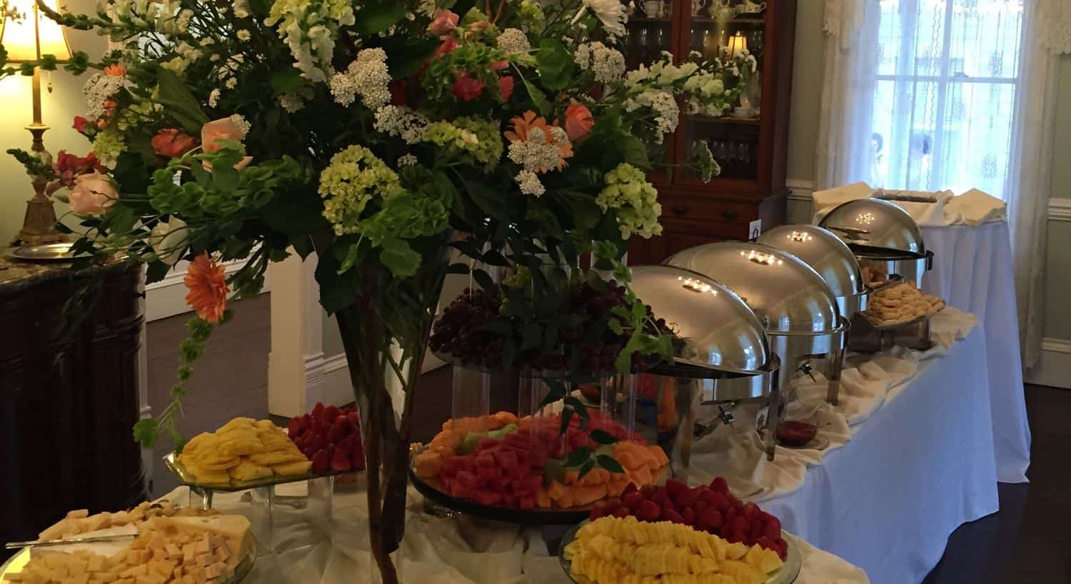 Wedding buffet table topped with silver food containers, fresh flowers and fruit and cheese platters